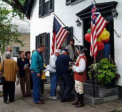 An accordion-playing guide welcomes visitors to a restored Dutch home in the Schenectady Stockade District.