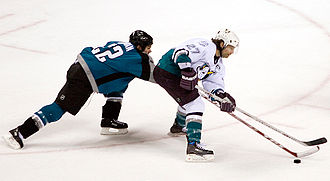 Anaheim Ducks - Scott Niedermayer battles for the puck with San Jose Sharks' Scott Hannan in a game during the 2005–06 season. Signed in the 2005 off-season, he was later named as team captain.