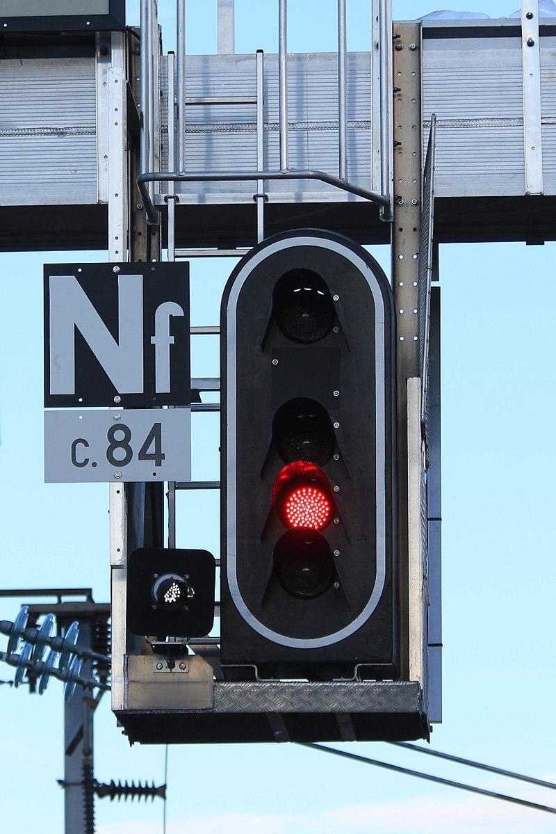 Feu SNCF oblong avec 4 feux plus œilleton dont un seul feu (rouge) est allumé, ainsi que l'œilleton (blanc).