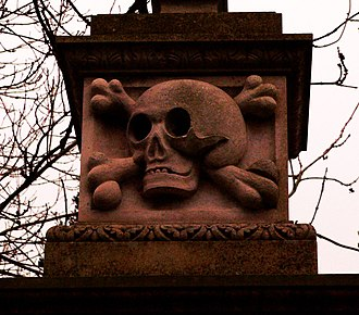 Kirkleatham - Statues of an elderly man and woman at Sir William Turner's Almhouses, Kirkleatham. The almshouses have been open continuously since 1676. The skull and crossbones gatepost is from the nearby Church of St. Cuthbert with the Mausoleum.