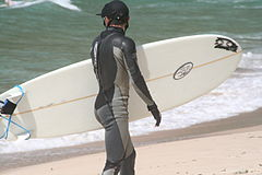 Surfer in wetsuit carries his surboard on the beach.JPG