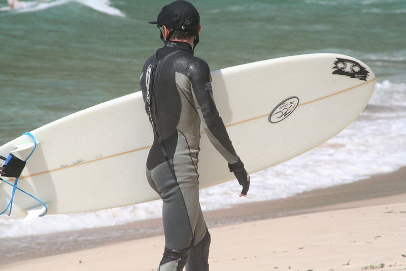File:Surfer in wetsuit carries his surboard on the beach.JPG