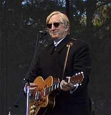 Burnett playing guitar onstage