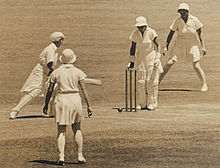 Monochrome image of four women on a cricket pitch, all the women are wearing white knee length sports dresses. The two players right by the stumps are also wearing pads, while the person behind the stumps (wicketkeeper) is also wearing gloves, the woman in front (batsman) is also holding a bat and looking at the stumps. The bowler has her back to the camera while the other woman in the frame is behind the wicketkeeper and facing the stumps.