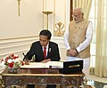 The President of Indonesia, Mr. Joko Widodo signing the visitor's book, at Hyderabad House, in New Delhi on December 12, 2016. The Prime Minister, Shri Narendra Modi is also seen.jpg