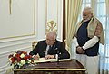 The Prime Minister of Malaysia, Dato' Sri Mohd Najib Bin Tun Abdul Razak signing the visitors' book, at Hyderabad House, in New Delhi on January 24, 2018. The Prime Minister, Shri Narendra Modi is also seen.jpg
