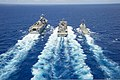 The amphibious assault ship USS Peleliu (LHA 5), left, and the guided missile destroyer USS Spruance (DDG 111), right, conduct a replenishment at sea with the fast combat support ship USNS Rainier (T-AOE 7) 140624-N-HU377-089.jpg