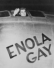 """A man waves from the cockpit window of a plane with the words """"Enola gay"""" written on it"""