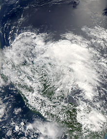 Satellite image of a large, disorganized mass of clouds near a landmass.