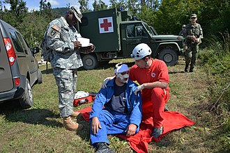 Roleplay simulation - U.S. Army Sgt. 1st Class Ahmad Whitted, standing, an observer-controller, monitors the interaction between a role player and a Slovenian Civilian Protection agent Aug. 25, 2014, in Postojna, Slovenia