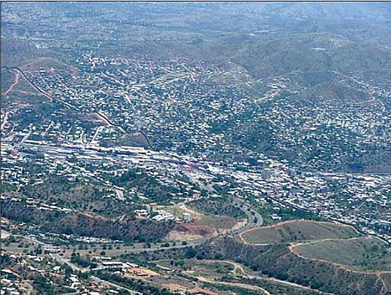 Aerial photograph of the United States-Mexican border, running diagonally from left to right, between Nogales, Arizona, United States, and Nogales, Sonora, Mexico (upper right) USMexicoborder.jpg