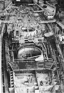 Black and white photograph of a ship under construction. The ship has not been fitted with its deck, and there are three large circular holes in the superstructure visible.
