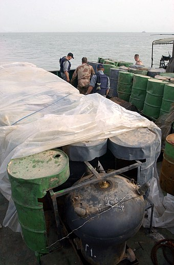 Camouflaged Iraqi mines hidden inside oil barrels on a shipping barge in the Persian Gulf, 2003. US Navy 030321-N-4655M-029 Coalition Navy Explosive Ordnance Disposal (EOD) team members inspect camouflaged mines hidden inside oil barrels on the deck of an Iraqi shipping barge.jpg