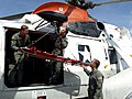 US Navy 040525-N-6639C-015 Hospital Corpsman 3rd Class Christopher Sandoval connects a rescue litter to the hoist of an UH-3H Sea King.jpg
