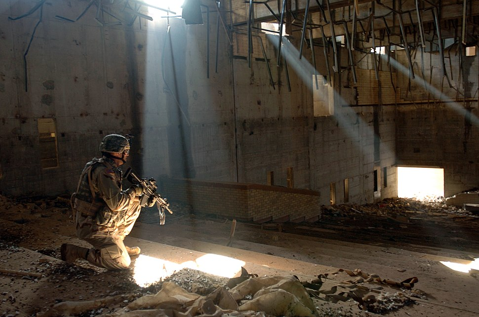 US Navy 060206-N-8252B-048 U.S. Army 2nd Lt. Amos Fox secures a building in a weapons compound in Hateen, Iraq, while providing security for the Ashurah pilgrims that will be passing through to Karbala