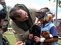 US Navy 070622-N-4238B-093 Capt. Bob Kapcio, USNS Comfort (T-AH 20) mission commander, adjusts the headgear of a local child.jpg