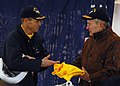 US Navy 080125-N-8544C-130 Capt. Kevin O'Flaherty, commanding officer of Precommissioning Unit (PCU) George H.W. Bush (CVN 77), presents former President George H.W. Bush with a yellow shooter's jersey.jpg