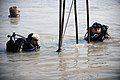 US Navy 091116-N-4154B-071 Navy Diver 2nd Class Zachery Dojaquez and an Iraqi Navy diver work together to run lifting wires from a crane to a sunken barge.jpg