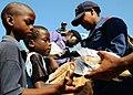 US Navy 100122-N-8655E-567 Logistics Specialist 1st Class Michauli Martin and Nigerian navy Capt. Adejimi Osinowo pass out bags of rice to Haitian civilians.jpg