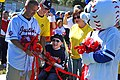 US Navy 111022-N-YR391-024 Senior Chief Missile Technician Jeff Norris and the Miracle League mascot hold a ribbon for a child to cut and officiall.jpg