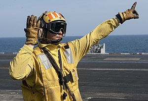 US Navy 120105-N-OY799-521 Aviation Boatswain's Mate 2nd Class Forrest Findley directs a fixed-wing aircraft on the flight deck of the Nimitz-class.jpg
