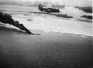 US Navy Helldiver flying over a burning Japanese tanker January 1945.jpg