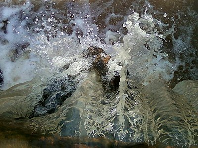 Water flowing onto a rock from a pond near Pandrangi village 01.jpg