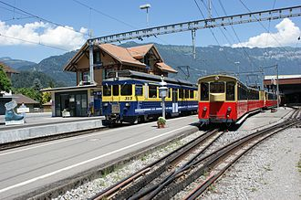 Bernese Oberland Railway - A train at the Wilderswil station with the track of the Schynige Platte Railway (red train) on the adjacent platform