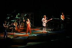 Una fotografía en color de los miembros de la banda Yes en el escenario.