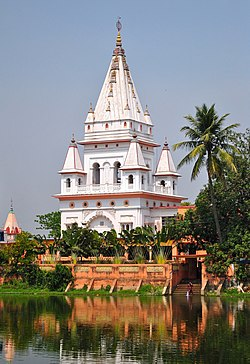 A white ornate structure with a pyramidal pointed dome standing on the bank of a pond and surrounded by trees