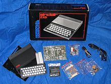 The component parts of the ZX81, including the case, keyboard and circuitry, resting on a blue sheet in front of the cardboard box in which it was shipped.