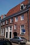 foto van Pand met brede lijstgevel voor oud pand onder hoog dwars schilddak met twee dakkapellen met frontons en hijsbalken