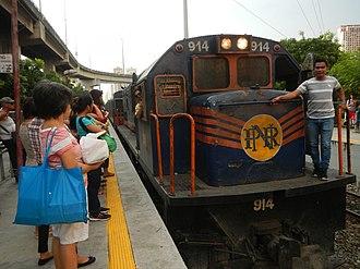 PNR Metro South Commuter Line - A PNR Class 900 (GE U14C/U15C)diesel locomotive hauling a former JR East 203 series set arriving at Pasay Road station