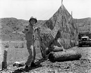 A man in military uniform constructs a net in a hilly outdoor environment