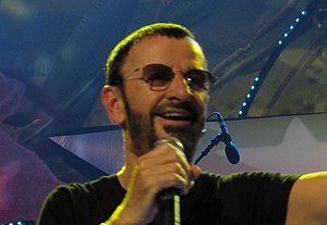 A colour photograph of Starr wearing sunglasses and singing into a microphone. The background is blue and purple.