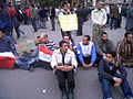 2011 Egypt protests - sitting line of men.jpg
