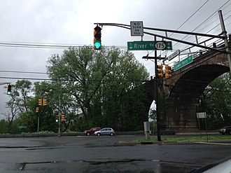 """New Jersey Route 175 - Intersection of Route 29, Route 175 and Lower Ferry Road in Ewing, with signage noting Route 175 as """"River Road."""" The West Trenton Railroad Bridge is in the background."""