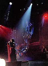 Image of a brunette woman in a black-and-red kimono moving to the right of a stage with red-lit backgrounds and a metallic tree like structure in the middle. A single source of light falls on her.