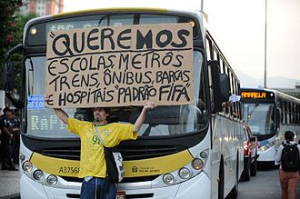2014 protests in Brazil - Protester holding a sign contrasting the quality of soccer stadiums with the quality of public services.