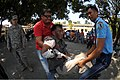A Philippine provincial health worker and a Philippine police officer carry a simulated burn victim as U.S. Army Sgt. 1st Class Cory Montague, left, evaluates their work during a mass casualty exercise at 130405-N-VN372-142.jpg