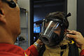 A fire-training instructor fastens the mask of U.S. Navy Seaman Elicia Guillory prior to her going inside a smoke and fire filled room during fire training at the Engineering and Firefighting School at Joint 101021-F-LX971-202.jpg