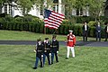 A flag detail and a bugler walk onto the South Lawn of the White House (48717847551).jpg