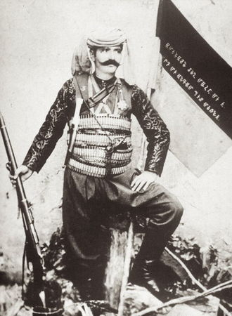 Andranik - An undated photo of Andranik holding a rifle. The text on flag seen in the background is from the poem The Song of the Italian Girl by Mikael Nalbandian, which became the Armenian national anthem in 1918. The lyrics are from the last stanza: Death is the same everywhere/A man dies but once/Blessed is the one that dies/For the freedom of his nation.