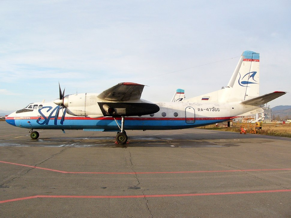 A blue and white An-24 regional aircraft parked on an airport apron