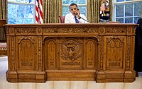 Barack Obama sitting at the ornate Resolute desk in 2009