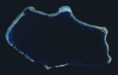 Bikini Atoll. On the northwast cape o the atoll, adjacent tae Nam island, The crater formed bi the 15 Mt Castle Bravo nuclear test can be seen, wi the smawer 11 Mt Castle Romeo crater adjynin it.