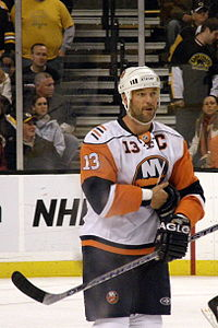 A Caucasian male wearing an orange, blue, and white jersey. Guerin is standing in a hockey rink, holding a hockey stick and has his right arm held against his stomach.