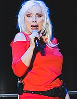 Debbie Harry looking to the right and holding a microphone