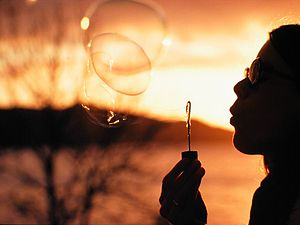 English: Blowing large soap bubbles at sunset