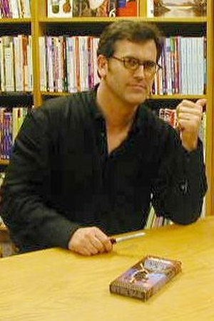 Bruce Campbell - Campbell signing a VHS copy of The Evil Dead at a fan meet-and-greet